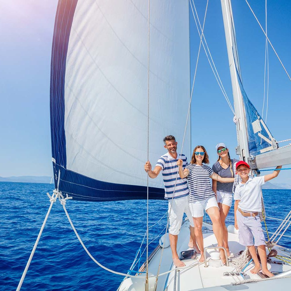 Family with adorable kids resting on yacht sailing on blue water