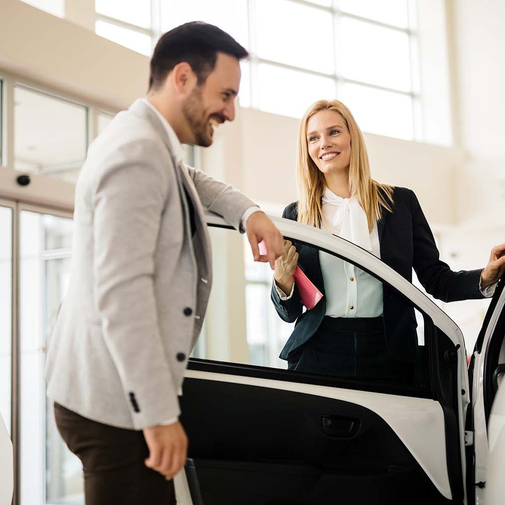Salesperson explains the benefits of car insurance to potential customer