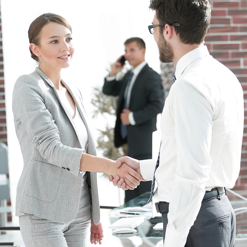 Business man shakes hands with his attractive female insurance broker.