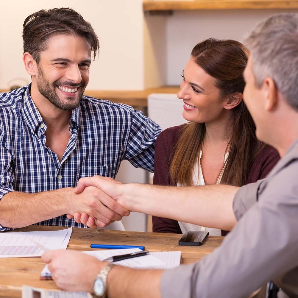 Insurance Broker shakes hands with client after signing insurance contract.